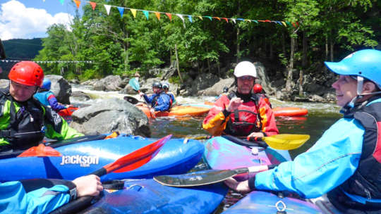 Group of kayakers all gathered on the river in a clump