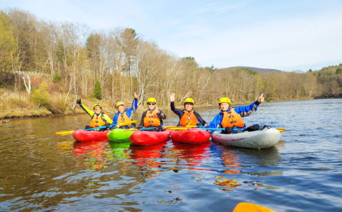 Group of kayakers lined up on the river during fall