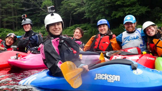 Woman in kayaks with go-pros on their helmets