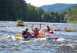 People smiling and waving as they kayak down a river