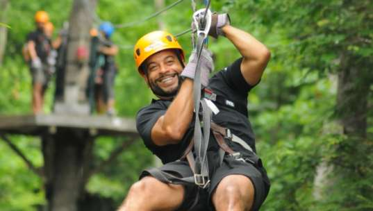 Man smiling as he zips through the forest