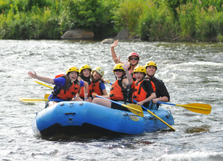 Group in a raft waving to the camera as they paddle on the river