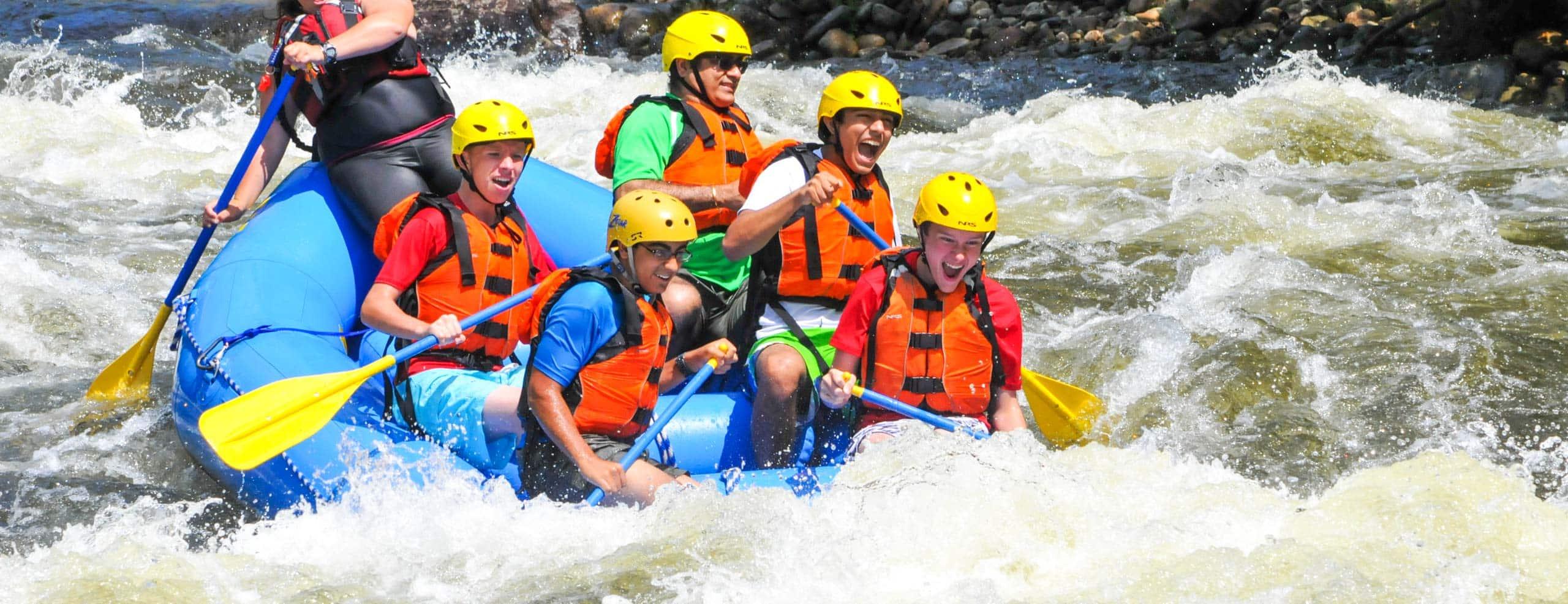Boys rafting down rapids