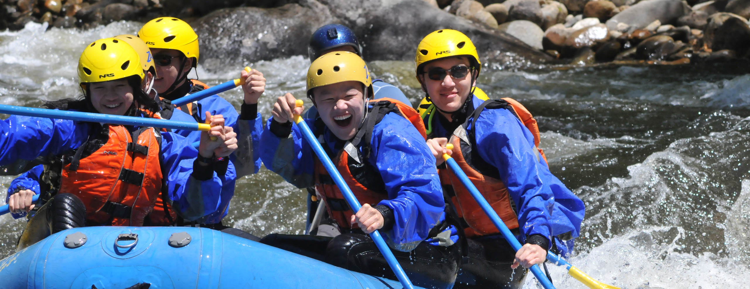 Group of people in a raft on the Dryway river having fun and smiling