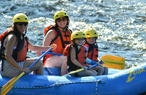 Two young girls and their mother in a raft floating down the river