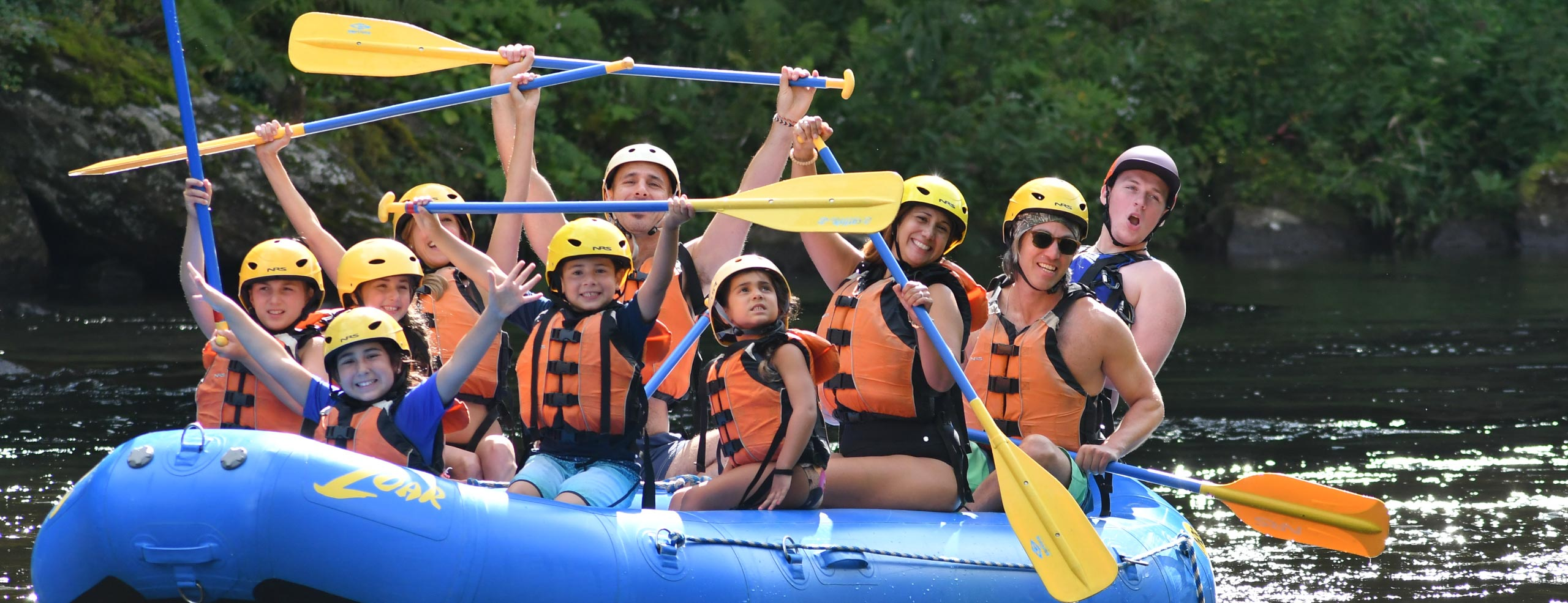 Family raising their paddles in enjoyment on the river