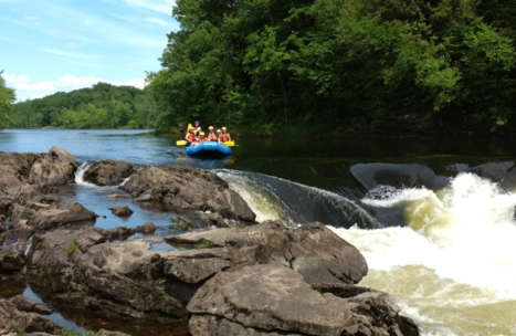 Group on a great fall rafting trip approaching a rock dam