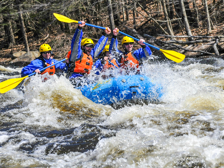 Group of adults in a raft going through rapids having fun