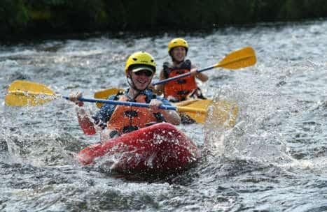 People kayaking through rapids