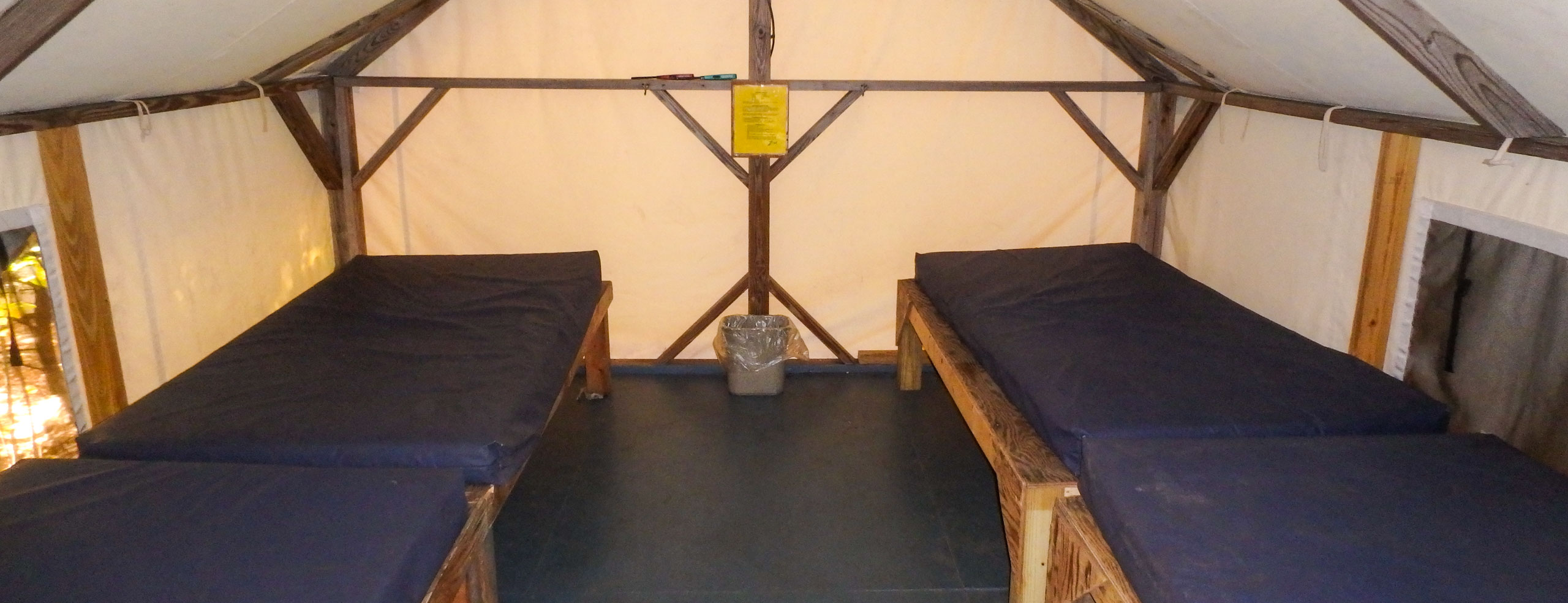 A cabin tent interior with two twin beds