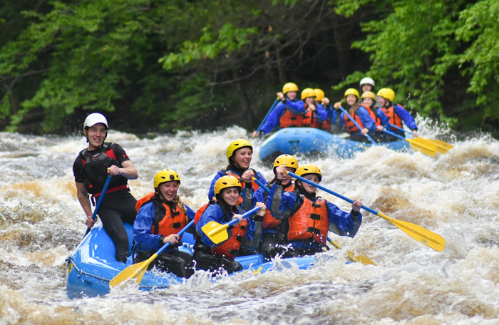 Group rafting down the Miller River on the adventure package trip