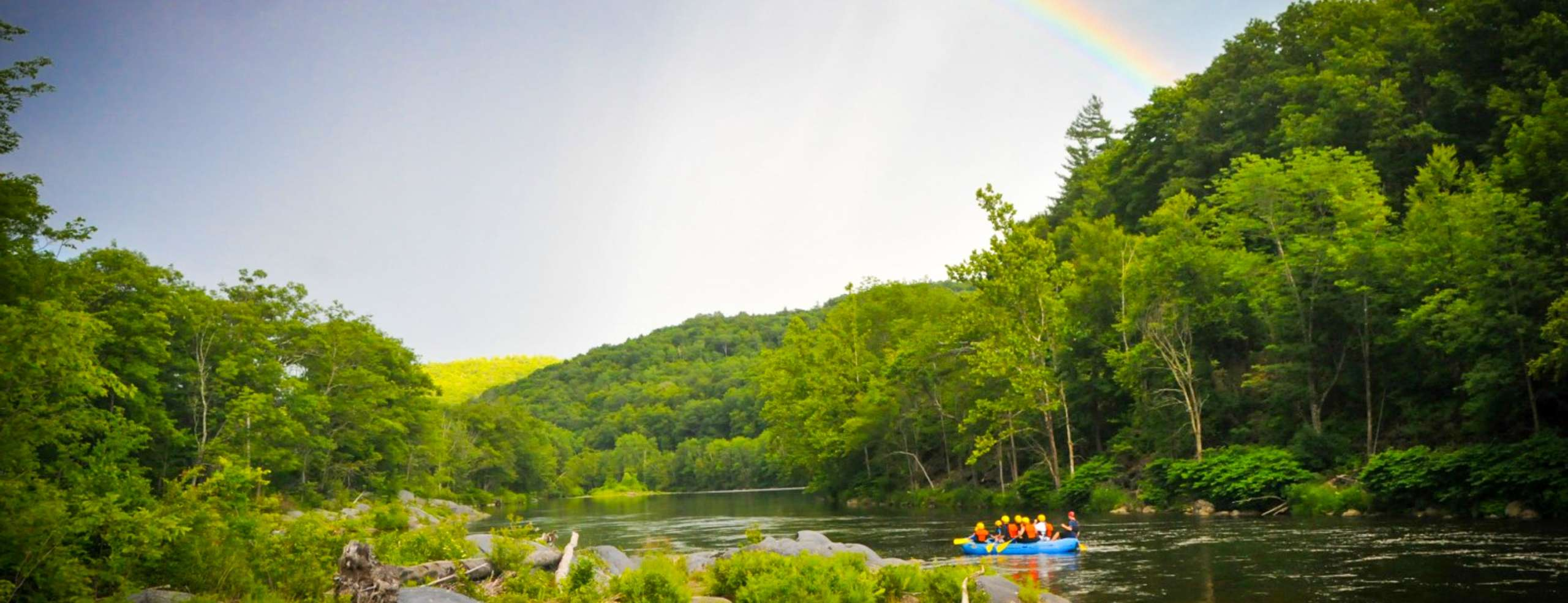 Rafting down a calm river with a rainbow in the sky