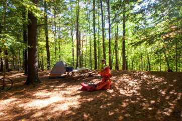 Camper setting up their tent in the woods