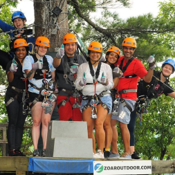 Group of zip liners taking a group photo on a tree platform