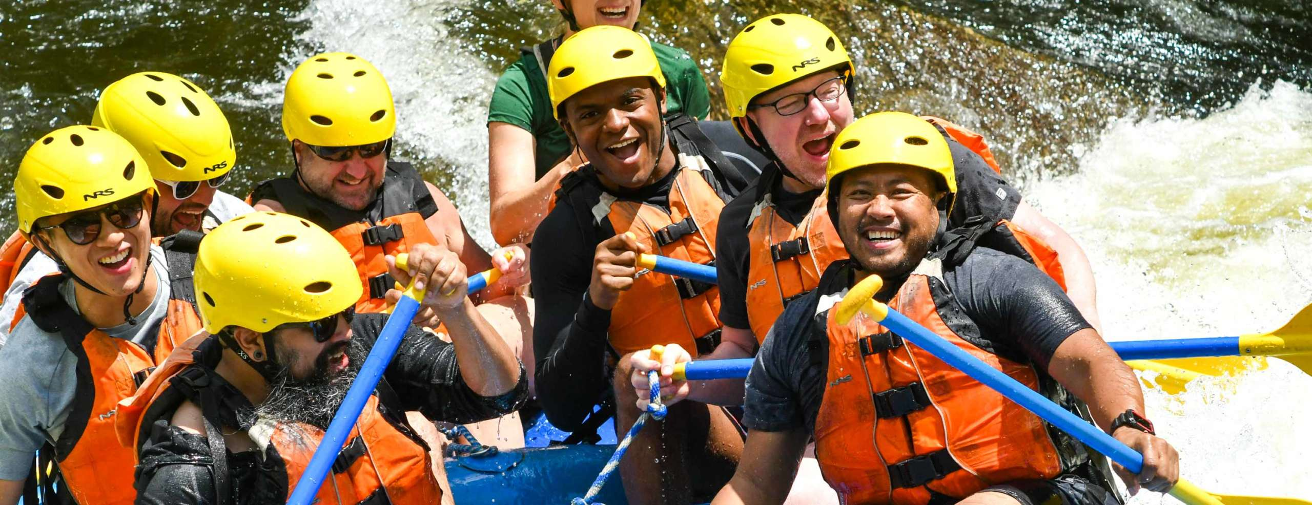 Group of smiling excited rafters rafting down a river