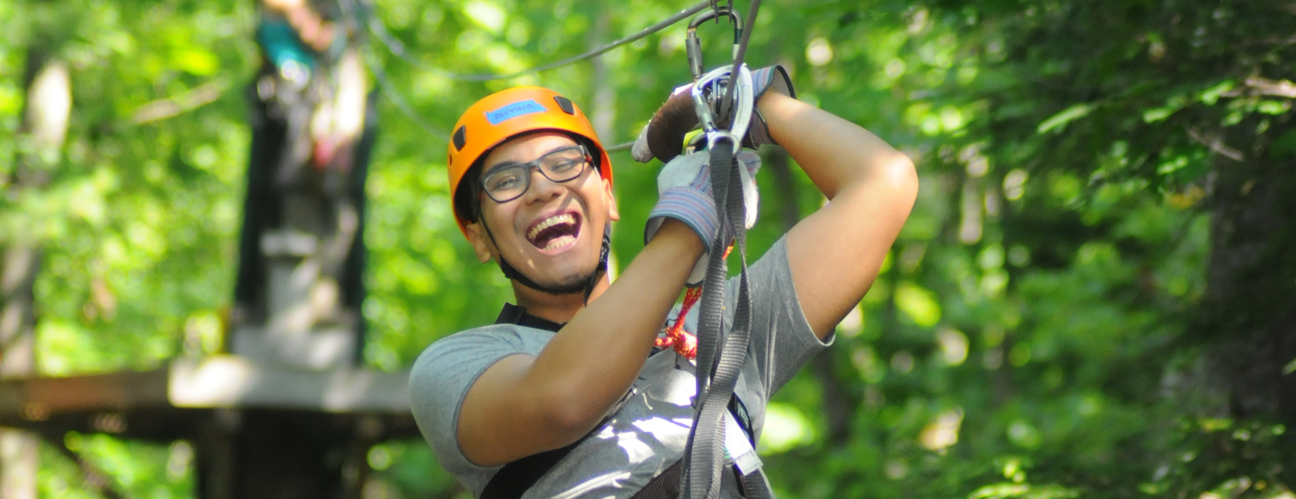 Man with a large open smile zipping through the trees
