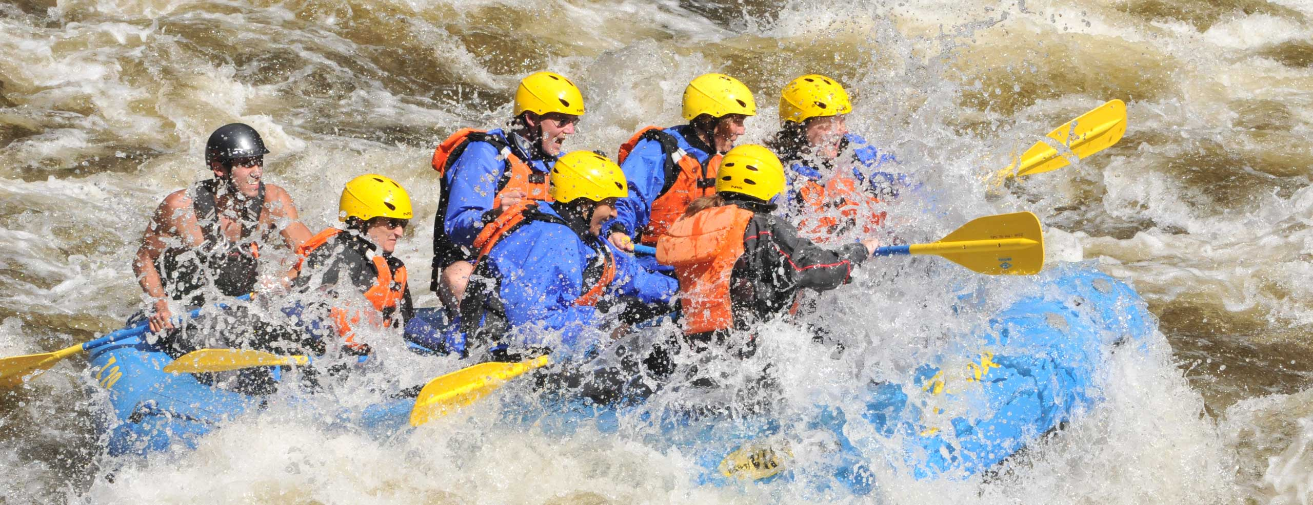 Group of rafters getting splashed and soaked by water from rapids