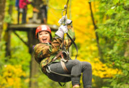 Young woman smiling as she ziplines through the forest