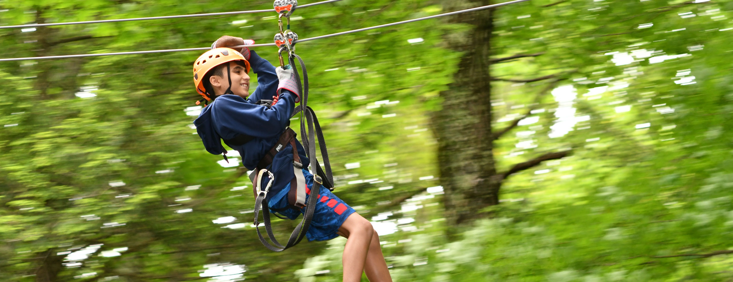 Young boy zip lining through the trees