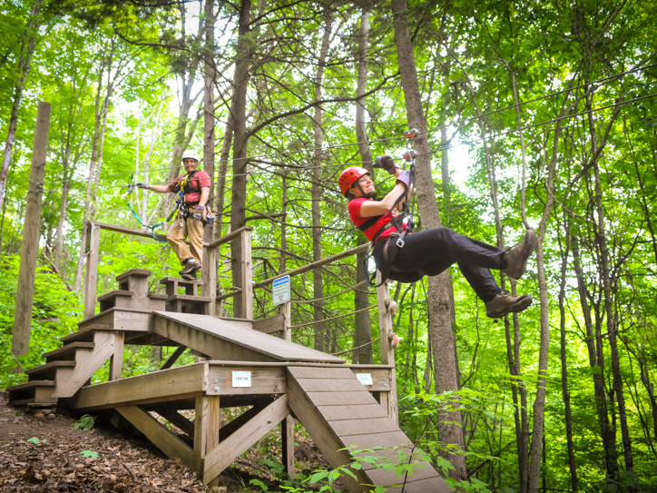 Woman zip lining down from a platform in the forest