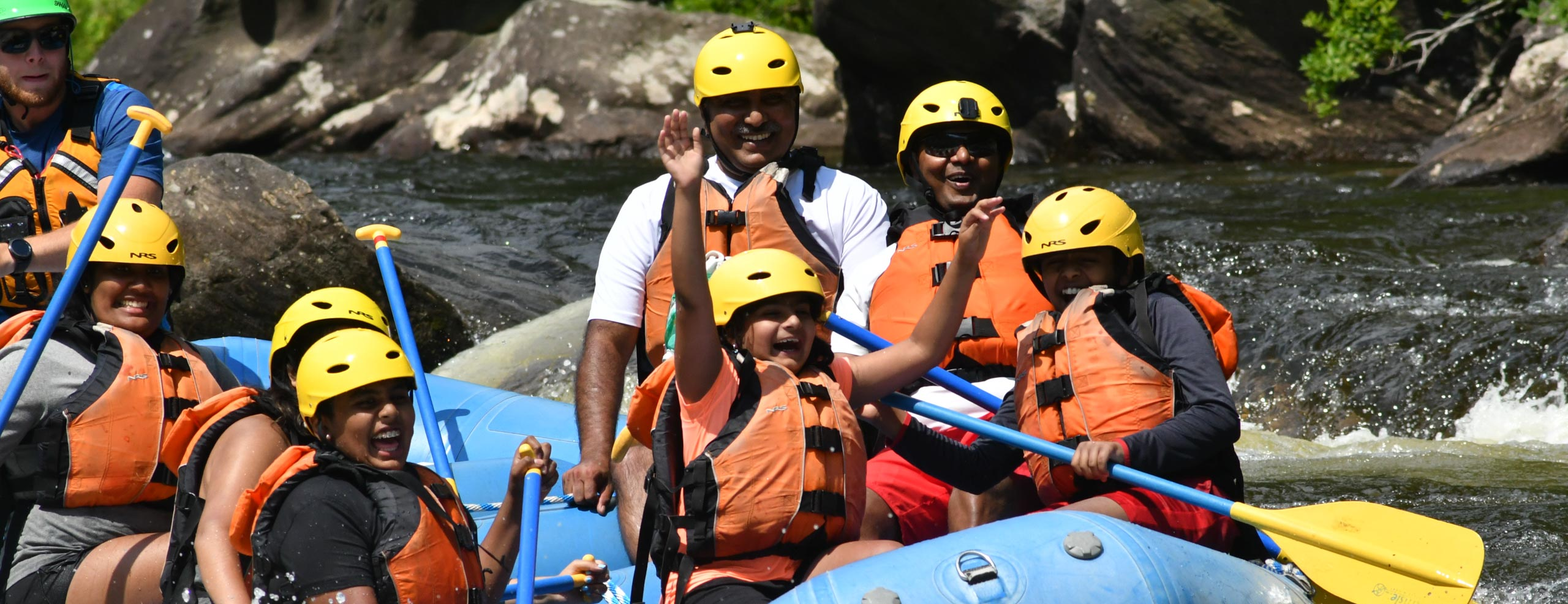 Group of people in a raft having fun and smiling during small rapids
