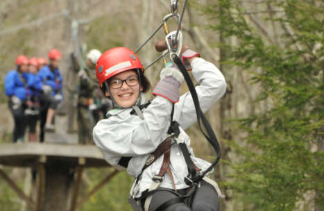 Young girl smiling as she zip lines through the trees