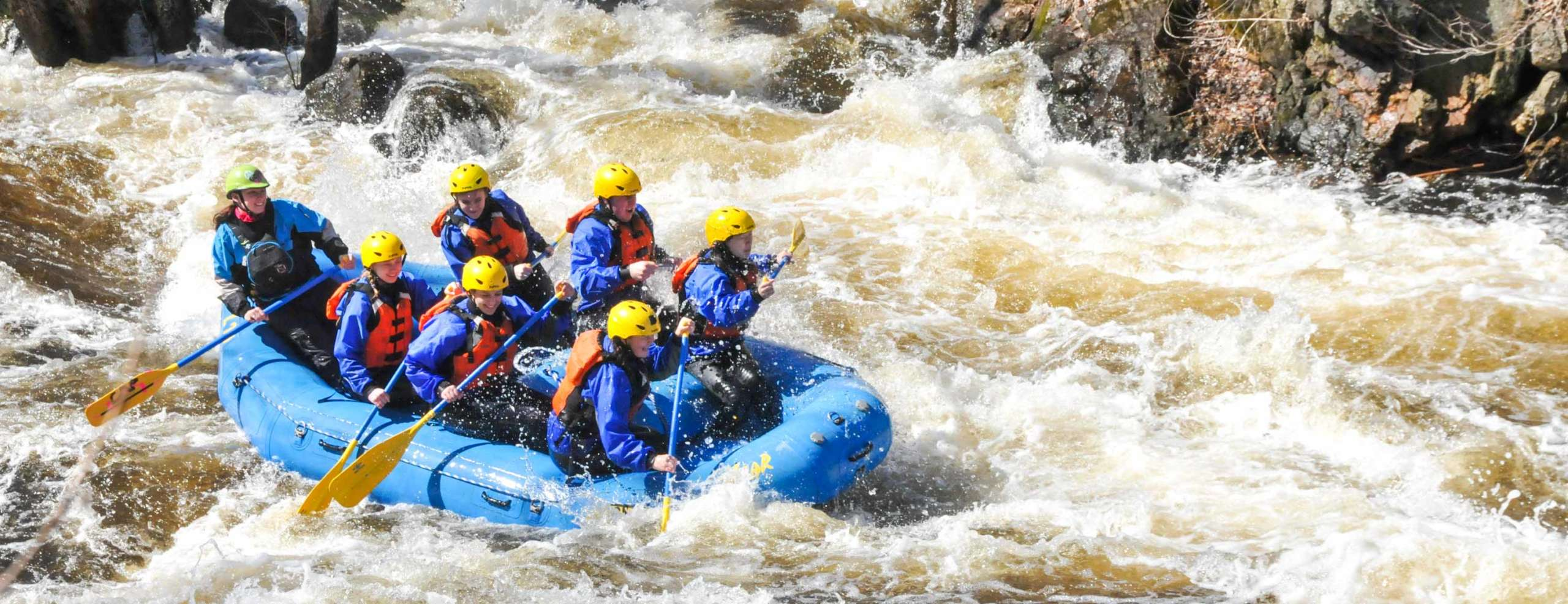 Group of people rafting through rapids