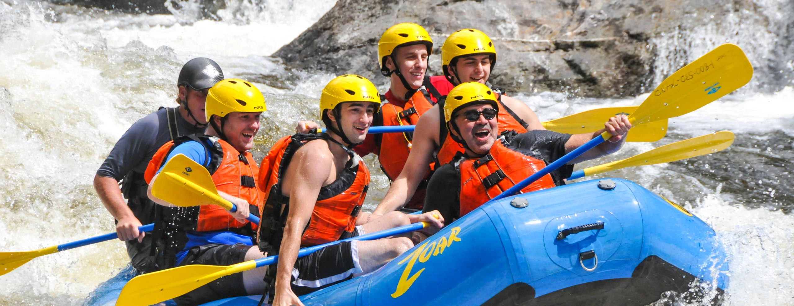 Group of guys in a raft navigating down rapids