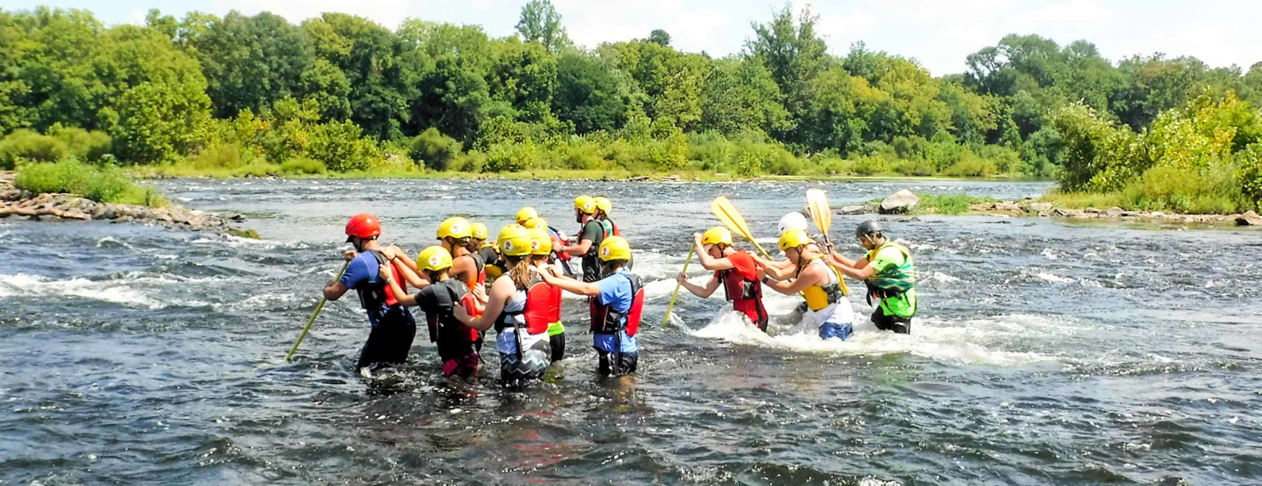 Group of youth learning to cross the river all holding onto each other