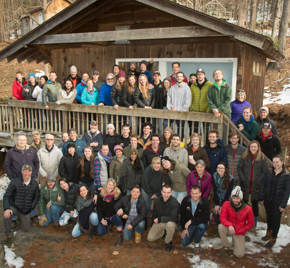 All staff outside of a cabin taking a large group photo