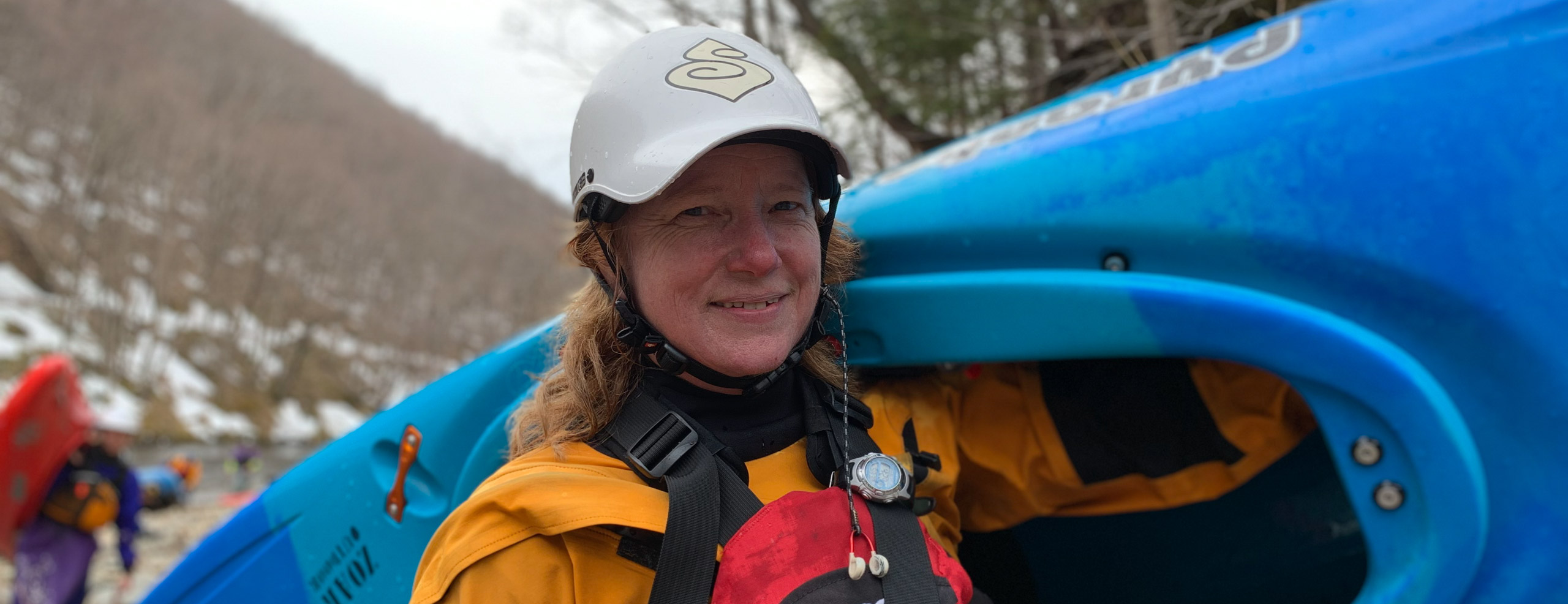 Janet holding her kayak on the river bank