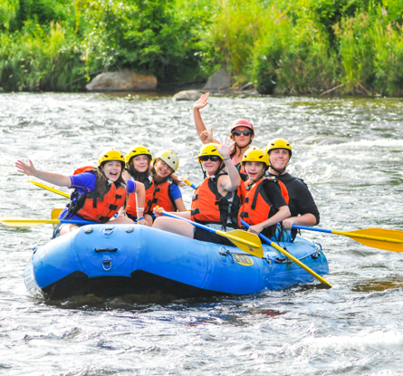 Group of young people in a raft waving to the camera looking excited