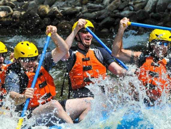 Group of rafters smiling as they paddle
