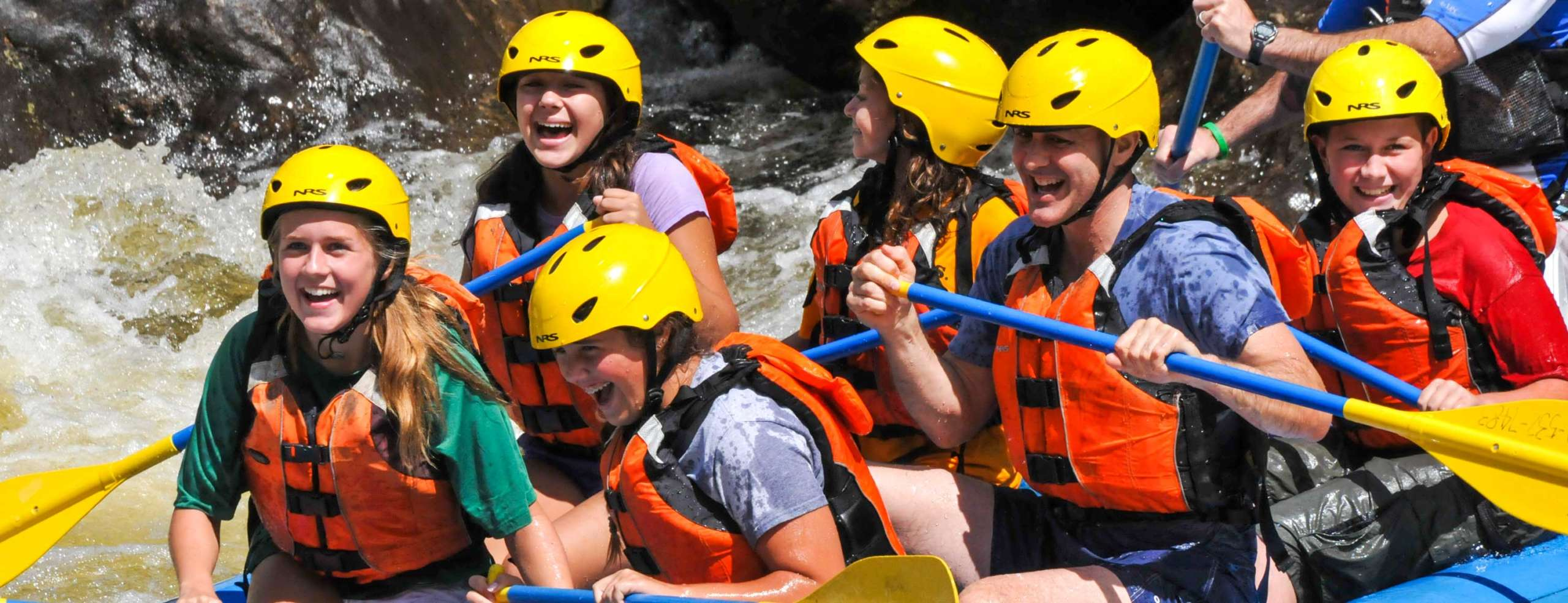 Group of young people rafting down a river