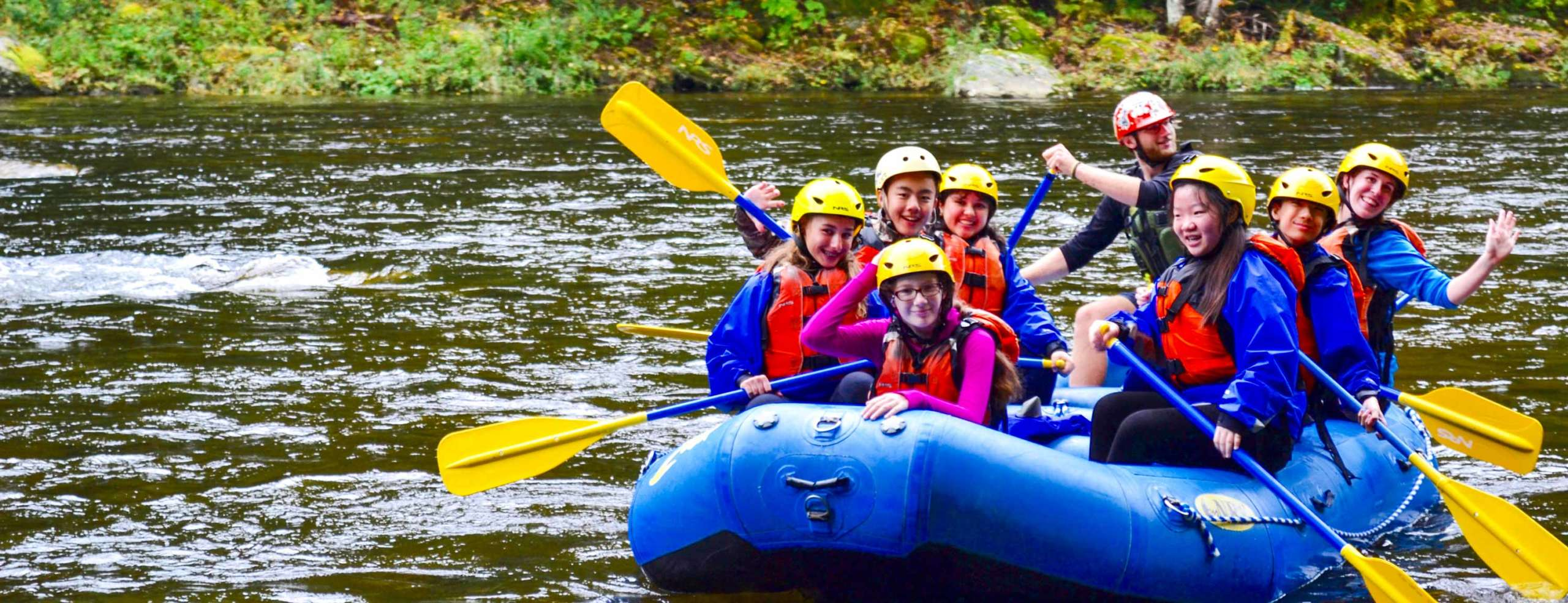 Youth group paddling a raft down a calm river