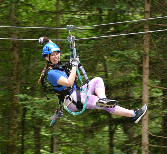 Girl in purple shorts zip lining through the tree canopy