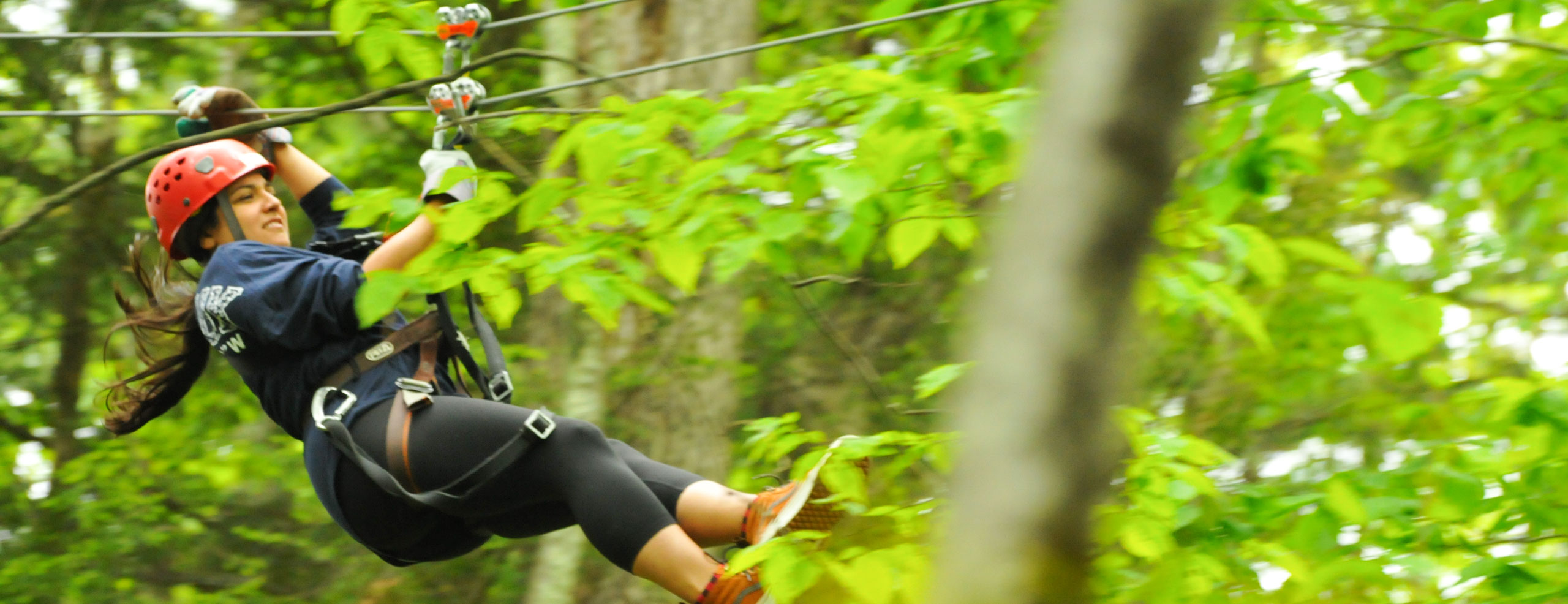 Woman zip lining through the trees