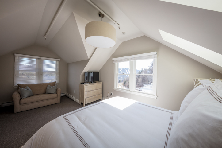 Bright light bedroom with queen bed and love seat