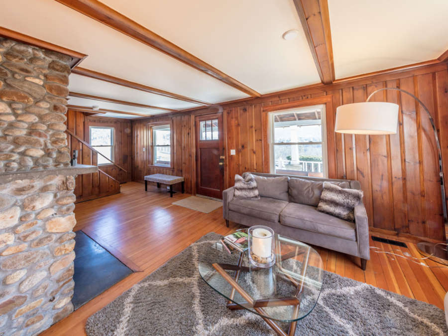 Large living room with wood floors a couch and fireplace