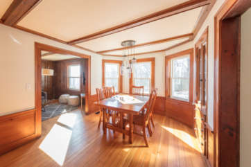 Bright dining room with wood floors and wooden table and chair set