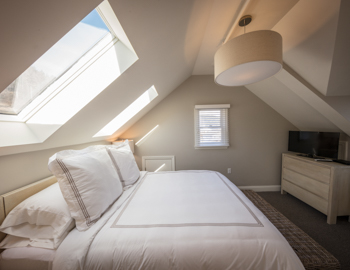 Bright light bedroom with queen bed and a bench