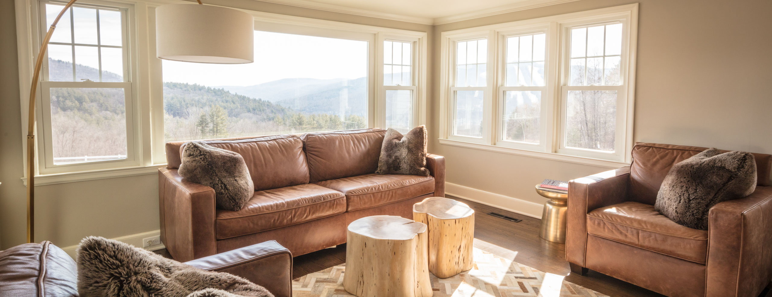 Bright light open living room with many seating areas and large windows