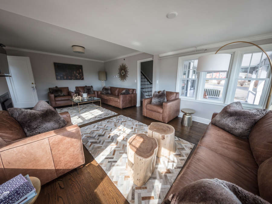 Large living room space with couches, arm chairs, and rugs