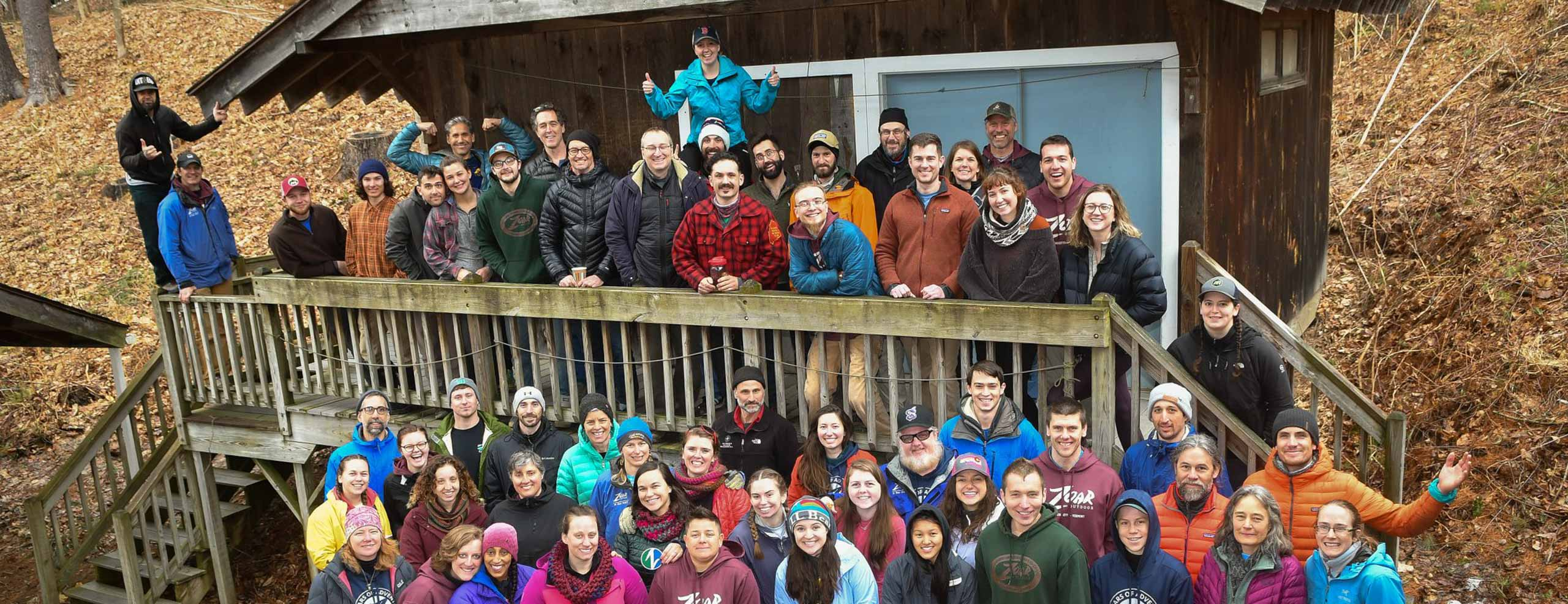 All of Zoar staff gathered outside on a deck for a group photo on a fall day