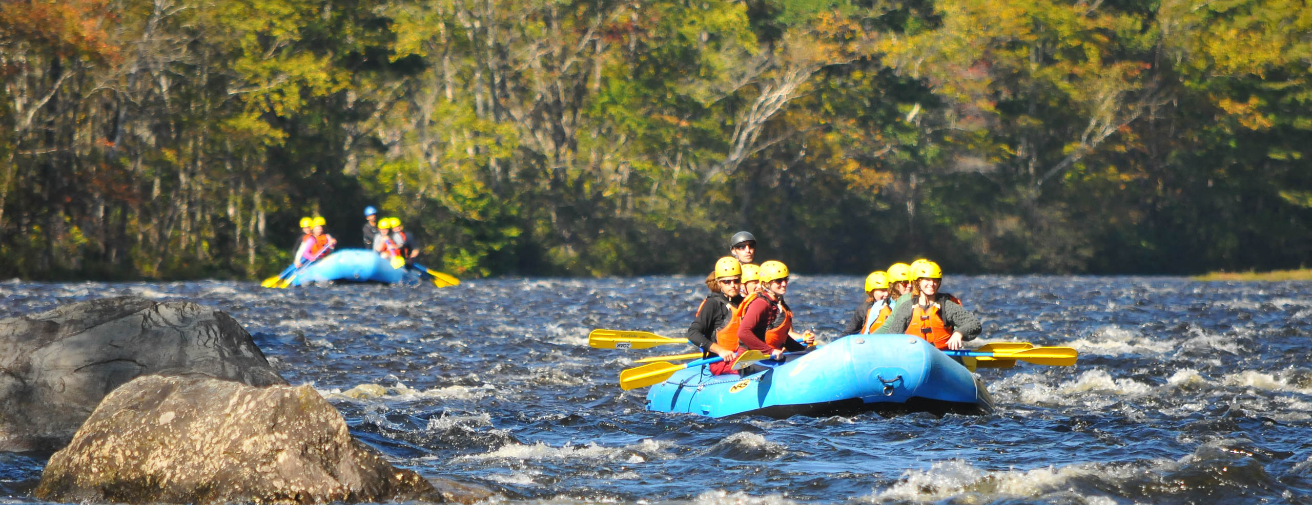 Two groups rafting down a river