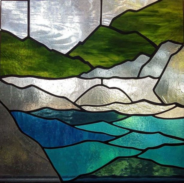 A stained glass work with a river with rocks and hills around it