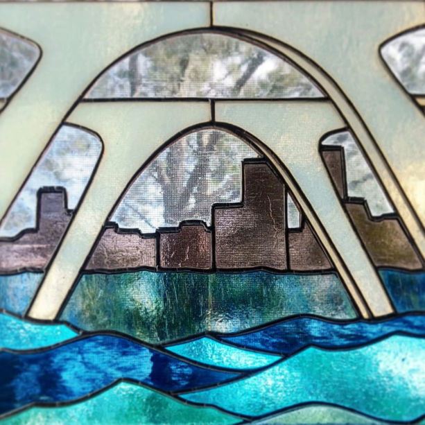 A stained glass work of the view underneath manchester bridge